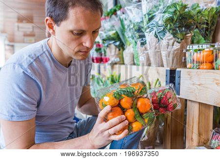 Young Man Picking Holding Plastic Boxes With Mandarin Oranges In Store