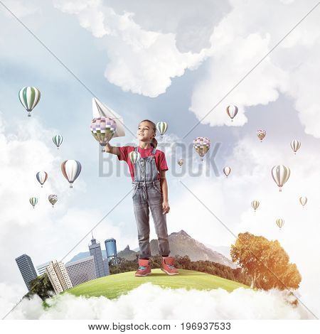Cute kid girl on city floating island throwing paper plane