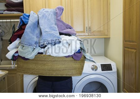 Woman Holding Basket Of Dirty Laundry In Home Room