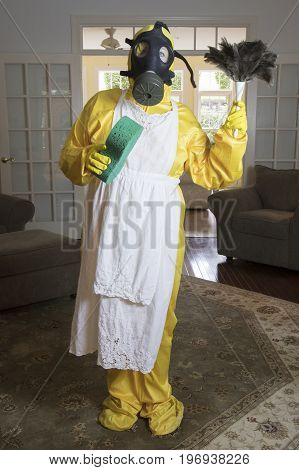 Mature Woman In Haz Mat Suit With Feather Duster And Sponge