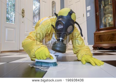 Mature Woman In Haz Mat Suit Scrubbing Floor With Brush
