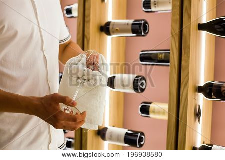 A young bartender is wiping towel wine glasses at work in the restaurant on the background of bottles of wine.