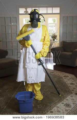 Mature Woman In Haz Mat Suit In Living Room With Mop