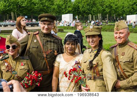 BERLIN - MAY 09, 2015: Group of soldiers in the form of the Red Army and the Polish Army photographed with a woman.