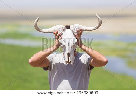Man holding a white wildebeest skull wearing it like a mask in nature on african wildlife safari, Amboseli national park, Kenya.