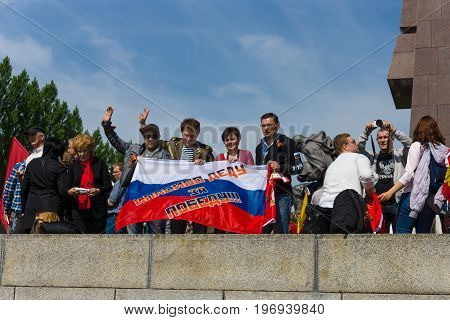 BERLIN - MAY 09, 2015: Visitors to the memorial with Soviet flags and patriotic slogans. The inscription in Russian: Thanks to his grandfather for the victory!
