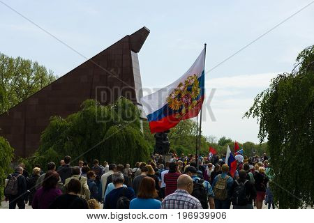 BERLIN - MAY 09 2015: Victory Day in Treptower Park. Visitors to the memorial with the flags of the USSR Russia and patriotic slogans.