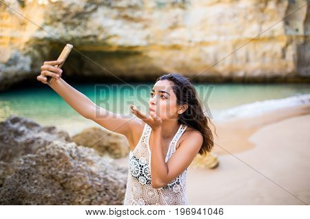 Beautiful Latin Girl Take Selfie On Phone At Beautiful Caves Beach Near Ocean. Summer Vocation Conce