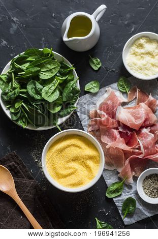 Ingredients for cooking - polenta spinach and prosciutto. Delicious lunch in a mediterranean style. On a dark background top view. Flat lay