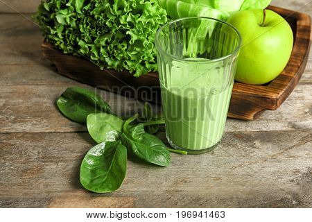 Glass of fresh juice on wooden background