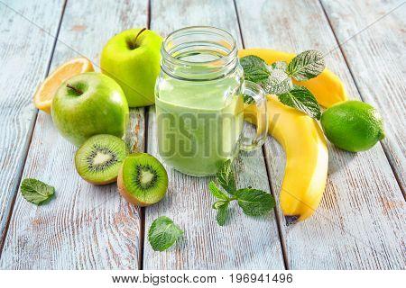 Mason jar of fresh juice on wooden background