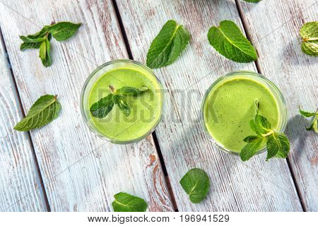 Glasses of fresh juice on wooden background