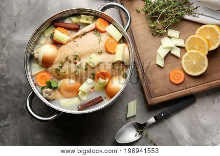 Composition with turkey soaked in cooking pot on table