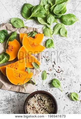 Healthy organic raw ingredients for making vegetarian lunch - butternut squash spinach wild rice on white background top view. Free space flat lay