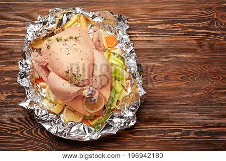 Whole raw turkey with other ingredients prepared to cook on wooden table