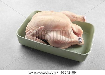 Whole raw turkey in casserole on grey background