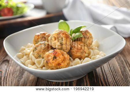 Bowl with turkey meatballs and pasta on table, closeup