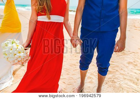 A picture of a happy couple holding hands at the beach. Relaxing at sunset during vacation. Newlyweds at the honeymoon. Close-up