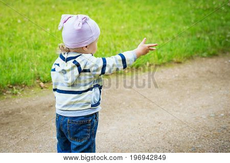 Child on road looks and shows his hand forward. child on footpath in park looks forward