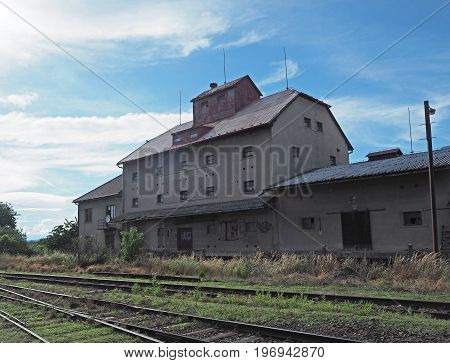 old empty house on railway with graffiti train line and blue sky