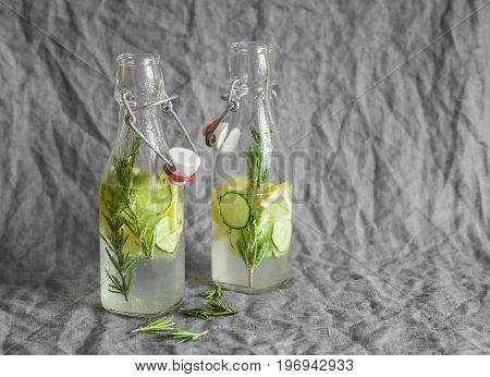 Rosemary lemon cucumber lemonade in vintage bottles on a grey background. Healthy refreshing drink