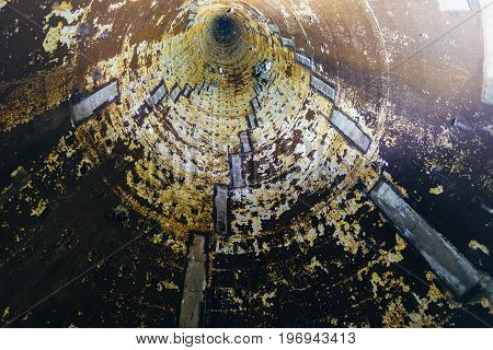 Bottom view. Rusty vertical mine tubing shaft