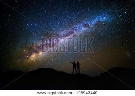 Landscape With Milky Way. Night Sky With Stars And Silhouette Of A Couple On The Mountain.