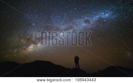 Landscape With Milky Way. Night Sky With Stars And Silhouette Of A Couple Kissing On The Mountain.