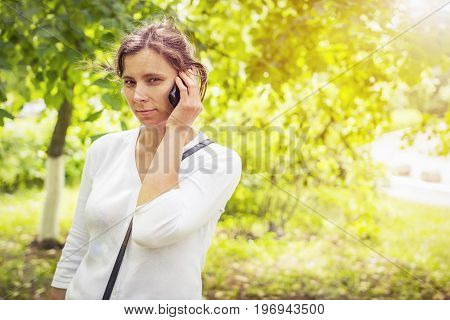 Girl hears sad news on phone. girl is calling on phone in green summer park