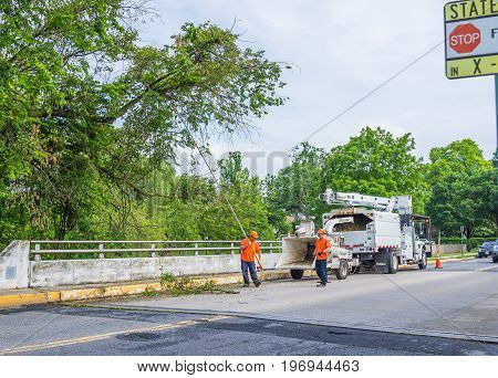 Frederick, Usa - May 24, 2017: Workers Cutting Down Tree Branch On Road Using Brush Chipper