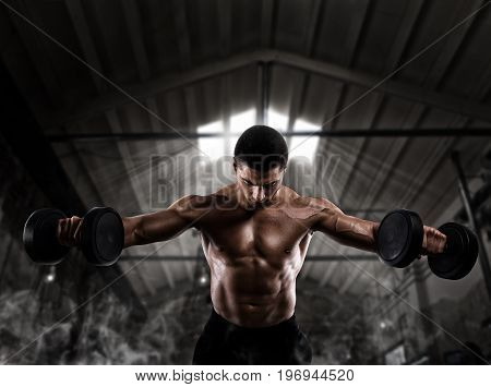 Athletic muscular man training biceps with dumbbells at the gym