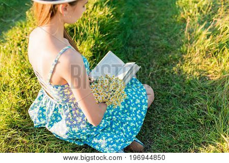 Young romantic girl in blue dress and hat sitting with an open book at sunset. The book is shooting from behind the girl's shoulder