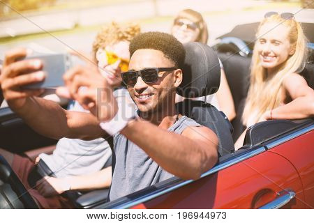 Young friends ready to vacation take a selfie in a cabriolet car