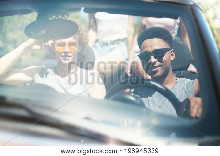 Young friends in cabriolet car ready to vacation travel