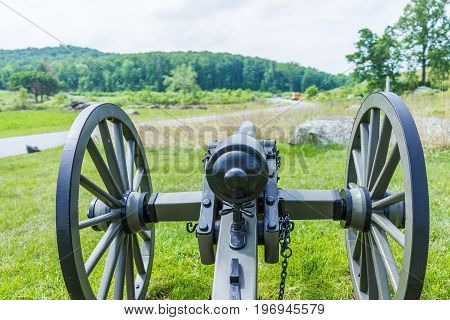 Gettysburg battlefield park with closeup of one cannon during summer and field with road