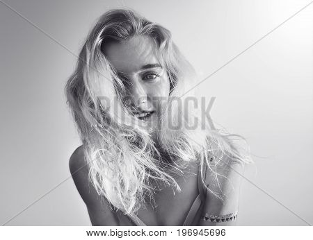 Pretty blonde haired woman posing on camera in light  swimsuit on the background of sky.Low angle. Black and white
