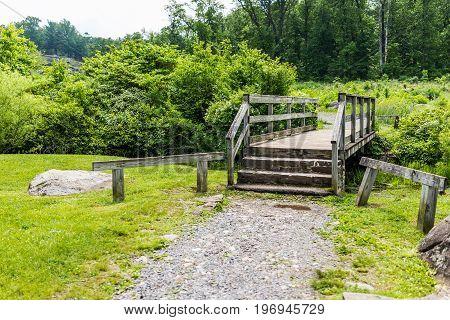 Wooden bridge and creek at Gettysburg battlefield national park landscape during summer with green field