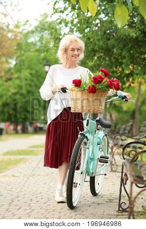 Beautiful middle aged woman with bicycle in park
