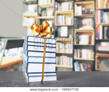 Books with ribbon bow as gift on table at library