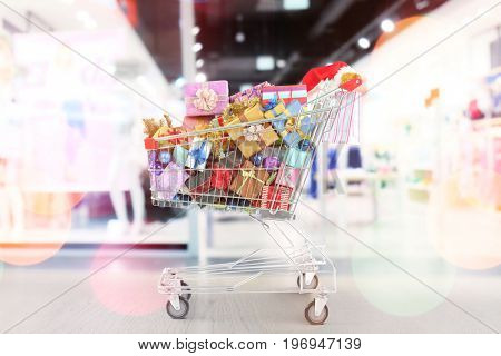 Market trolley with gifts at shopping mall. Boxing day concept