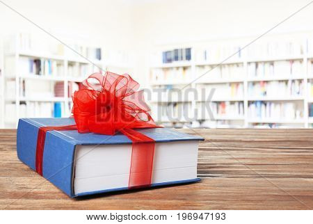 Book with ribbon bow as gift on wooden table at library