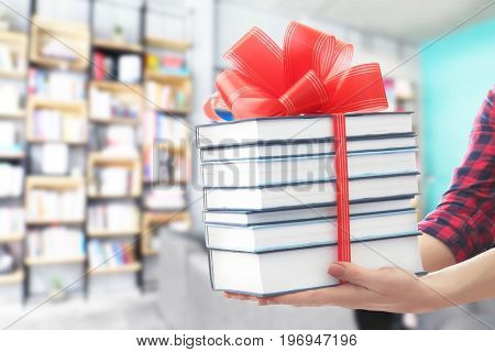 Woman holding books with ribbon bow as gift at library
