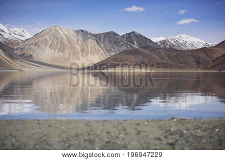 Reflection of Mountains on Pangong Lake with blue sky background. Leh, Ladakh, India.