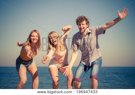 Friendship happiness summer holidays concept. Group of friends boy two girls having fun outdoor stretching arms celebrating