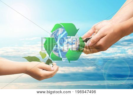 Mother and child hands with globe and sign of recycling on sky background. Ecology and environment conservation