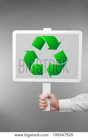 Man holding board with sign of recycling on grey background. Ecology and environment conservation