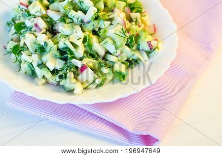 salad with radishes, cucumber greens and green onion sauce served on the side