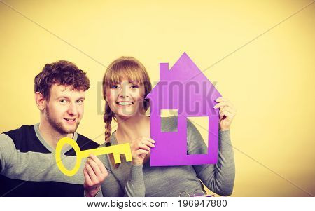 Dream and new plan for living. Young joyful smiling people thinking dreaming about their first house. Couple with big key to their future.