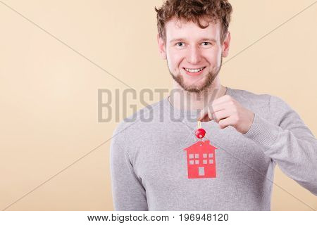 Young bearded smiling man holding new house key with red home shape. Real estate and housing concept.