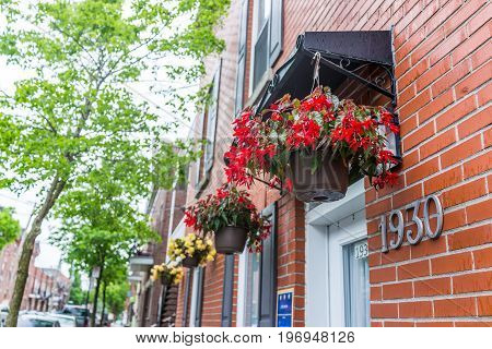 Montreal, Canada - May 26, 2017: Hanging Red Flower Pots On Brick Building In Urban Area